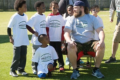 Photo of cofounder of Bear General Contractors Josh Sitton with community youths